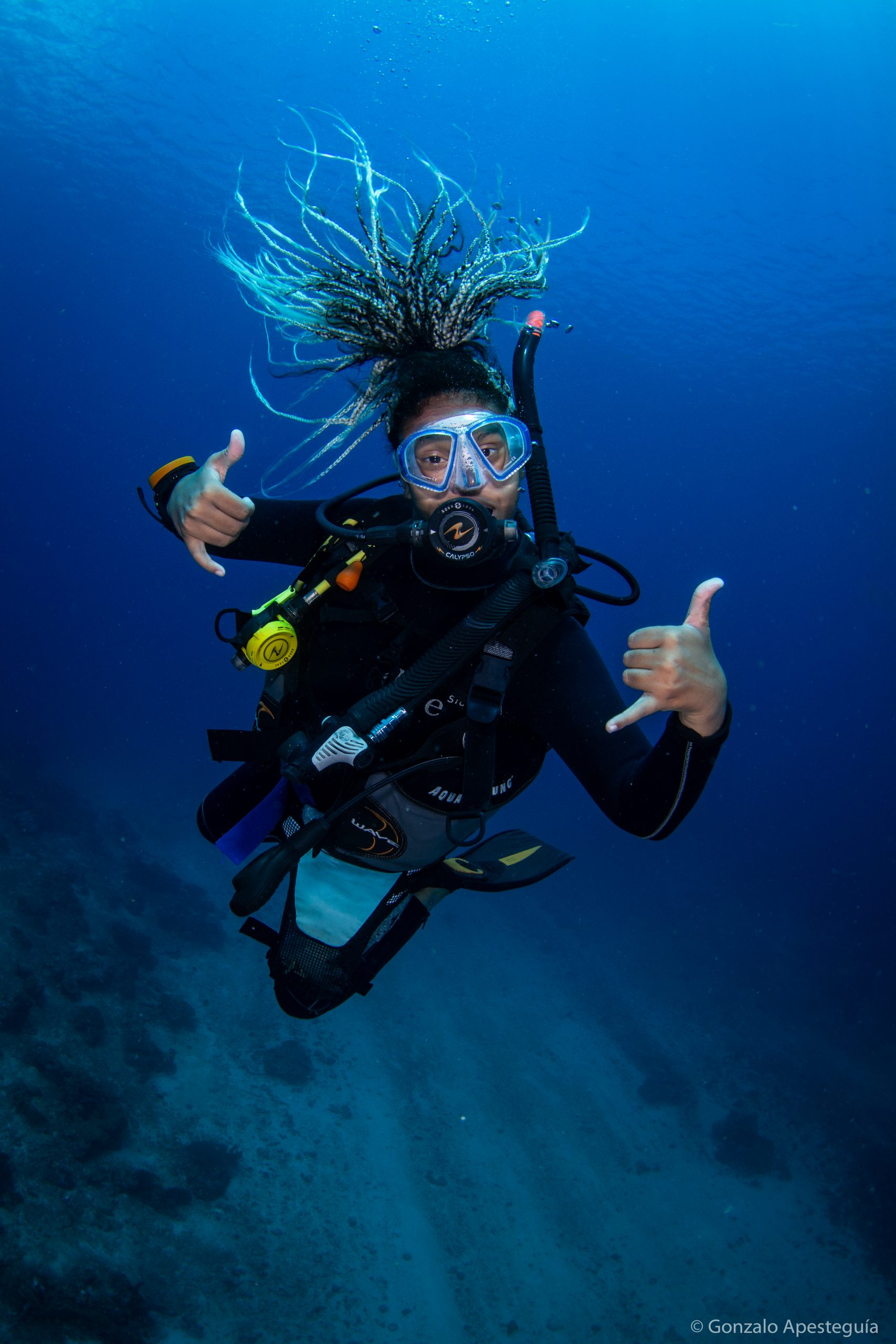 Female scuba diver with dreadlocks which gives the hang loose hand signal